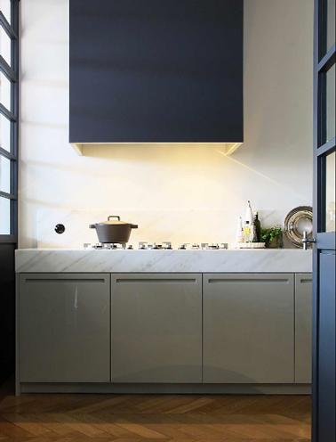 Une déco moderne pour une cuisine de maison de campagne avec une peinture pour les boiseries bleu électrique qui contraste avec le style authentique des meubles de cuisine taupe.