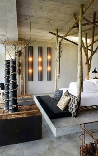 déco chambre avec lit baldaquin fabriqué avec des troncs de bois et plateau table basse en planches de récup