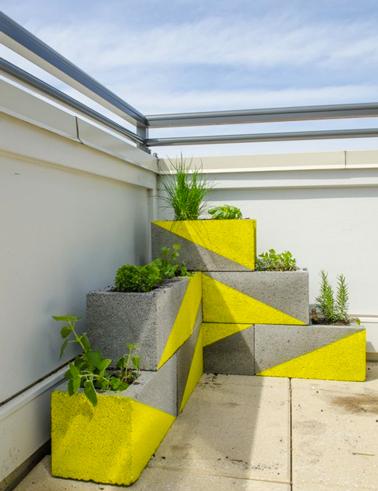 Jeu graphique avec la peinture pour décorer des jardinières en parpaings. Du jaune, gris et vert c'est sympa sur une terrasse en ville !