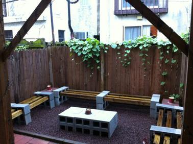 Dans un petit jardin en ville à l'abri des regards derrière les cloisons de bois, des parpaings assemblés en bloc pour faire la table basse, et une association futée de bois et parpaings compose les bancs.