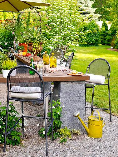 Sur les pieds en parpaing le plateau de la table de jardin en teck apporte le côté chic