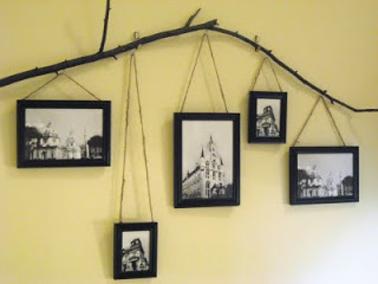 Pour une déco originale des cadres photos dans le salon, une branche d'arbre set de support aux cadres qui sont suspendus à différente hauteur à l'aide du corde.