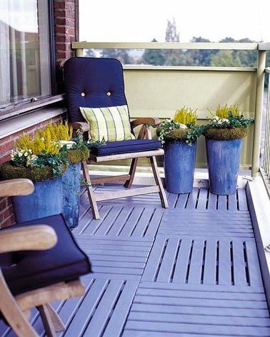 aménager un balcon avec une déco tout en bleu et vert: au sol, caillebotis peint bleu lavande assorti à la couleur des jarres. Pour profiter du soleiln deux fauteuil en teck et coussins bleu marine