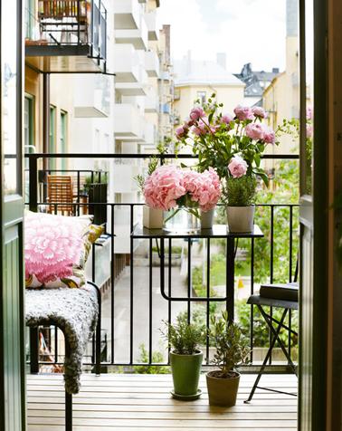 Un tout petit balcon aménagé en prolongement du séjour avec des touches de vert et rose pour l'égayer