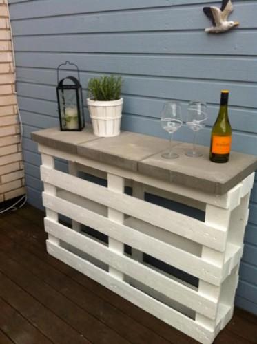 un bar pour le jardin fabriqué avec une seule palette bois peinte en blanc pour fabriquer le pied sur lequel sont posé des carreaux en béton pour le plateau