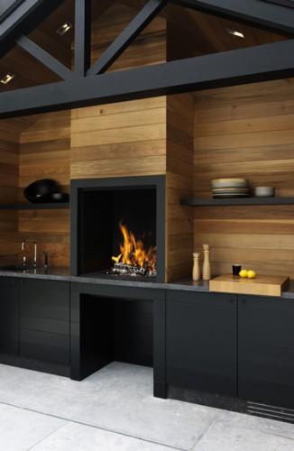 Cuisine extérieure pour un été design dans le jardin.  Conduit de cheminée et mur en teck clair, meubles de cuisine en stratifié noir ébène.