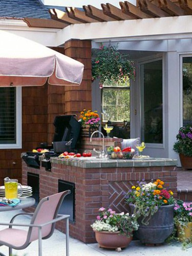 Cuisine dété aménagée près de la maison avec un bloc en briques rouge pour intégrer évier et barbecue. Plan de travail en carreaux gris imitation béton