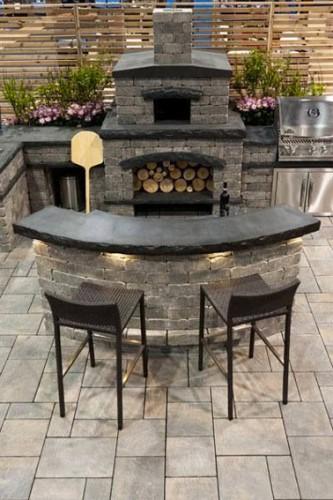 Une cuisine extérieure tout confort installée sous une pergola. Construction en pierre, plan de travail en ardoise avec four à pizza avec niche pour réserve bois et barbecue inox