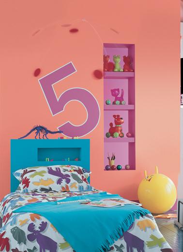 décoration du mur de la tête de lit dans une chambre d'enfant avec niche de rangement et pochoir grand chiffre 5. Peinture couleur bleu, saumon et rose fushia Astral