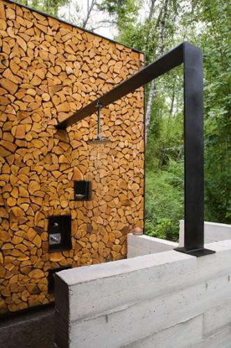 Douche de jardin installée sur poutre métallique en L qui s'appuis sur un mur monté avec des buches de bois.