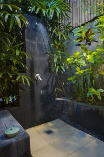 Douche de jardin installée dans un havre de végétation et de pierres noires. Au sol un carrelage de grands carreaux de pierre beige