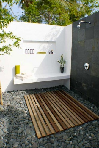 douche de jardin installée dans deux murs d'enceinte peints en blanc et gris anthracite. sur un des murs un petit banc en  béton. Au sol un caillebotis en teck