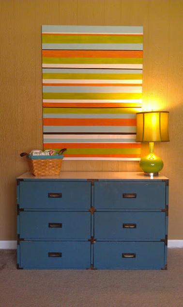 Une décoration pour le mur du salon avec un tableau fabriqué avec des bandes de peinture de plusieurs couleurs sur une plaque de bois.