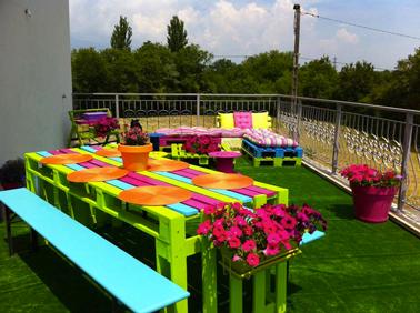 Une table en palette haute en couleurs avec des palettes en bois peintes en vert anis, fushia et bleu azur. 2 palettes bois servent à construire les pieds de la table