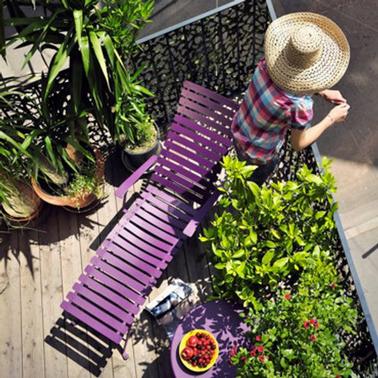 De la couleur pour aménager un petit balcon apportée avec un transat et une petite table couleur violet pour faire un contraste avec les plantes vertes