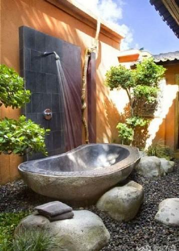 Une douche d'extérieure avec une baignoire en pierres pour receveur  installée dans un environnement aux couleurs magiques et un sol de gros galets.