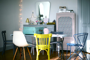 Des chaises dépareillées c'est tendance pour la déco de la salle à manger. Dans celle-ci, la seule chaise jaune sert à casser à la monochromie de bleu vert