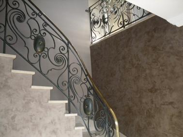 Peinture à la chaux ferrée ultra brillante sur murs escaliers. La teinte chaudeTabac Brun de la chaux est mis en contraste avec le mur peint gris souris pour sublimer le magnifique escalier en marbre