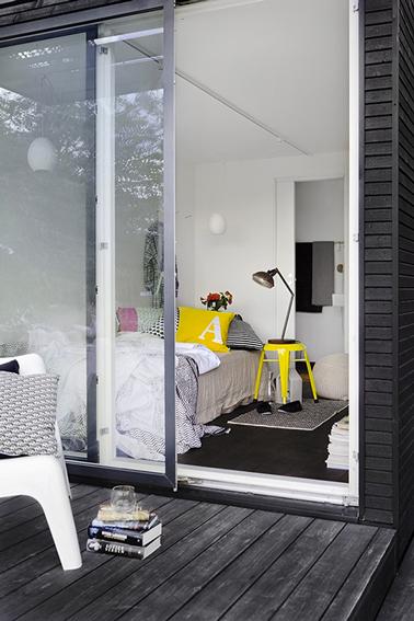 Harmonie de teintes grise et de blanc dans cette chambre de fille rehaussée par un tabouret Tolix jaune citron qui sert de table de chevet