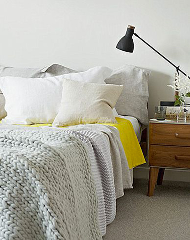 Dans cette chambre couleur lin en total look, loin d'être un intrus, le drap jaune apporte une note de fraicheur vivifiante