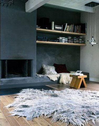 Dans ce salon moderne, un gris ardoise recouvre l'ensemble du mur intégrant également la cheminée pour un contraste forte avec les autres murs gris perle. Le parquet chêne clair ainsi que les étagères bois apportent la note chaude