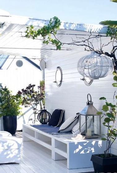 Pergola sur terrasse ambiance ile de Ré blanc et bleu avec toit en plaque PVC ondulé et transparant. Le ban est construit sur mesure avec dalles béton peint en blanc