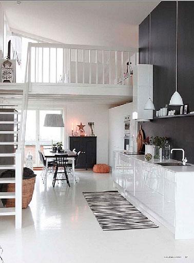 Dans un espace ouvert sur le salon salle à manger, une cuisine blanche mise en valeur par un mur et crédence noir qui fait ressortir l'aspect ultra brillant des façades des meubles