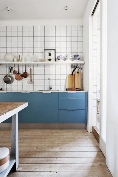 La peinture couleur bleuet pour repeindre les meubles de cette cuisine donne de la classe et une touche moderne à la faïence murale blanche conservée dans son jus. Le parquet et la table en bois apportent une note chaleureuse qui compense la dominante de couleurs froides.