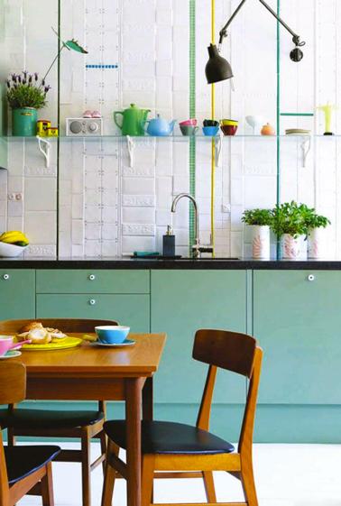 Le vert émeraude utilisé pour repeindre les meubles de cuisine est  repris en écho pour le listel de la crédence est mis joliment en contraste avec le blanc du carrelage et du sol