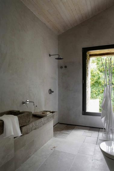 Authenticité d'une déco minimaliste pour une ambiance zen dans cette salle de bain aux murs en béton et carrelage au sol gris réchauffés par le lambris bois du plafond en pente
