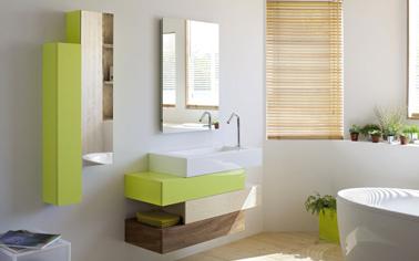 Ambiance zen dans la salle de bain avec un meuble sous-vasque Aubade hyper léger composé de blocs superposés en décalé et 3 finitions : bois noyer et bouleau et laqué vert anis. Pour tamiser la lumière un store à lames en bambou clair.