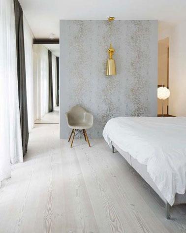 Déco minimaliste dans cette suite parentale où une astucieuse cloison grise sépare l'espace dressing de celui dédié au coucher