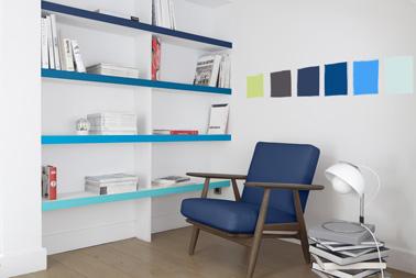Des touches de peinture bleu pour booster un salon blanc réalisées avec la peinture Colorissim V33 pour peindre les bords des étagères et  la décoration murale.