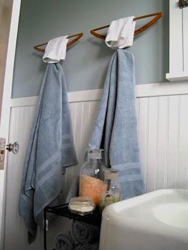 Des cintres en bois crochés au mur à l'envers deviennent des porte-serviettes de toilette hyper sympa dans la salle de bain