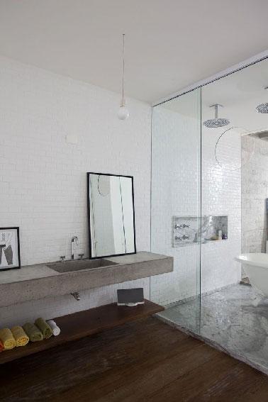 Une salle de bain qui mise sur la pureté des lignes des éléments sanitaires et la sobriété des couleurs pour offrir un espace de détente.