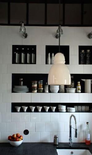 Dans le mur en carrelage blanc au dessus du plan de travail d'une petite cuisine, des niches peintes en noir pour le rangement de la vaisselle blanche, une solution esthétique et pratique pour gagner de la place