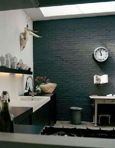 Dans la cuisine d'une maison de campagne le mur de brique peint en noir avec les autres murs blanc confère à la pièce un esprit design renforcé par les lignes épurés du plan de travail noir et blanc