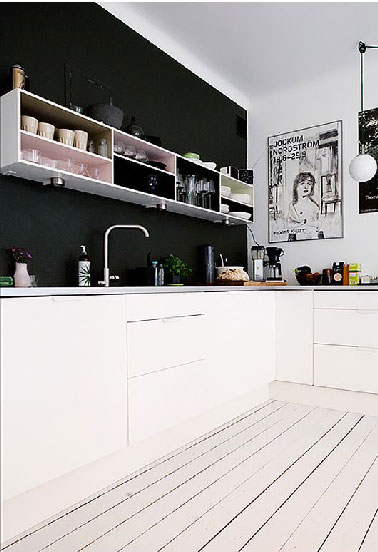 Dans cette cuisine blanche le mur de la crédence peint en noir s'anime du damier formé par les meubles hauts sans portes où certains fonds ont été retirés