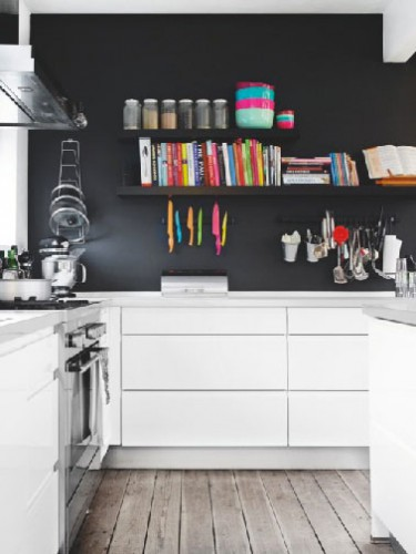 L'élégance du noir sur le mur du fond d'une cuisine blanche agencée en L. Pour compléter l'ambiance design, un plan de travail en Corian gris perle, le tout sublimé par l'apport chaleureux du sol en parquet chêne grisé