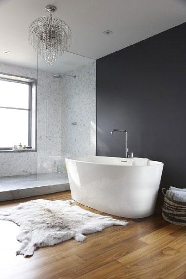 La rénovation d'une salle de bain dans une maison ancienne qui a permis de d'installer une estrade pour y placer la douche italienne. Le parquet restauré et vitrifié apporte une touche chaleureuse à l'ambiance où gris et blanc dominent.