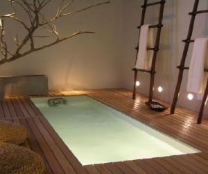 salle de bain zen aménagée dans un espace dédié à la détente et au bien-être avec une baignoire XXl et un sol en parquet bambou