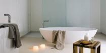 Une baignoire îlot, du bois, des couleurs douces dans la salle de bain et l'ambiance zen s'installe. Pour accentuer le bien-être des spots et éclairages tamisés, une paroi de douche en verre sablé, la décoration de la salle de bain privilégie les matériaux naturels