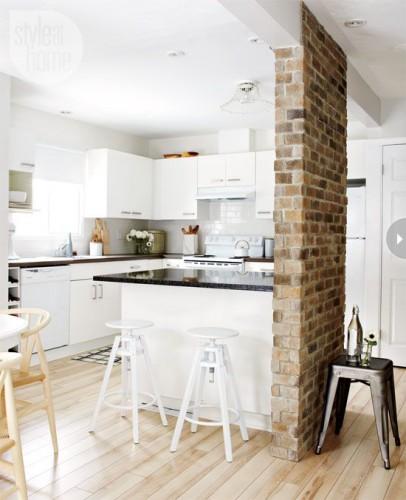 Un mur en brique donne le cachet à cette grande cuisine scandinave. Les meubles de cuisine couplés à la peinture et au parquet blanc apportent la chaleur d'une déco scandinave conviviale