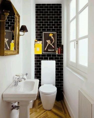 """Une déco dans des WC, même petits, c'est possible ! Ces WC aux allures de petits couloir proposent une déco minimaliste qu augmente l'espace au départ restreint. La disposition des lattes du parquet clair en """"flèche"""" donne un effet de profondeur supplémentaire à ces toilettes.  Les touches de jaune apportent de la couleur dans ces WC tandis que le miroir et la fenêtre s'allient pour estomper l'effet étroit et donner une meilleure luminosité à la pièce."""