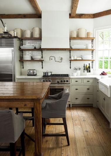 Familiale et conviviale la déco d'une cuisine vintage passe aussi et surtout dans les détails. Dans cette cuisine, la table, les étagères et le parquet en bois réchauffent l'atmosphère blanche de la crédence de la cuisine et des meubles.
