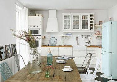 Pour un design total vintage de votre cuisine, misez sur le bleu, rose, vert d'eau, des couleurs en vogue pour la maison dans les années 50. ici, le réfrigérateur Smeg remet le design et les courbes douces des années après guerre au goût du jour. Le vaisselier ancien, la tableen bois brutet leschaises dépareillées renforcent encore l'aspect rétro de la cuisine. Summum de la rencontre du vintage et de la modernité: le parquet peint en forme de damier noir et blanc.