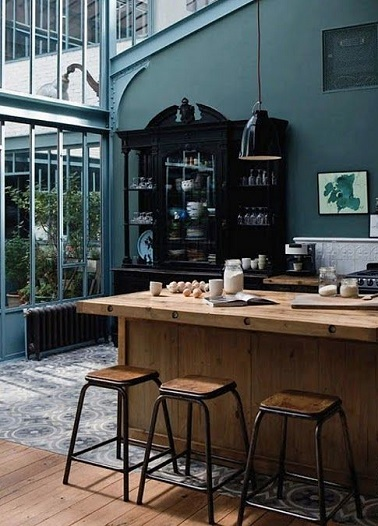 Le bleu pétrole offre à toutes les pièces une certaine classe. Dans cette cuisine aux murs et verrière bleu des meubles en bois un style industriel chic gagne la cuisine.