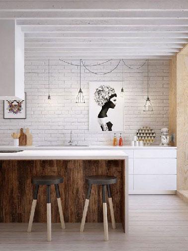 une blancheur immaculée dans cette cuisine scandinave. Des meubles en bois design apportent la modernité tout en conservant son esprit initial. Le style nordique est garantit grâce à la présence d'un mur en briques blanches et de poutres apparentes .