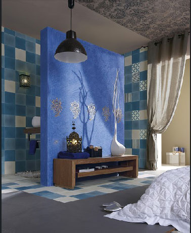 Dans cette suite parentale qui ne manque pas de charme, la salle de bain aménagée directement face au lit se cache derrière une cloison recouverte d'un superbe bleu sur lequel scintille des décors argenté réalisés avec peinture dorure Syntilor. Des carreaux de ciment bleu ciel et blanc dans l'espace bain donnant dans une chambre, il fallait osé, c'est fait et réussi ! Autre liberté prise dans cette chambre : des lés de papier peint posé sur une partie du plafond structure les différents espace de la pièce et conforte le style baroque recherché pour la décoration de cette chambre qui ne manque de caractère.