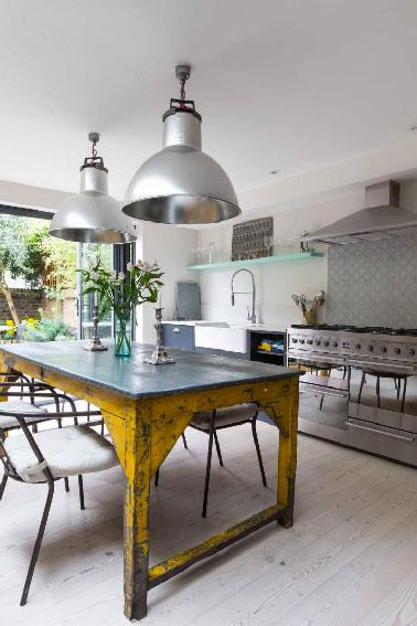 Dans cette cuisine, la crédence se pare de motifs rétro gris se mariant parfaitement avec l'inox omniprésent dans la pièce. La table en acier brut d'origine industrielle offre une touche de couleur jaune bouton d'or éclatant qui dynamise la dominante de blanc et gris.